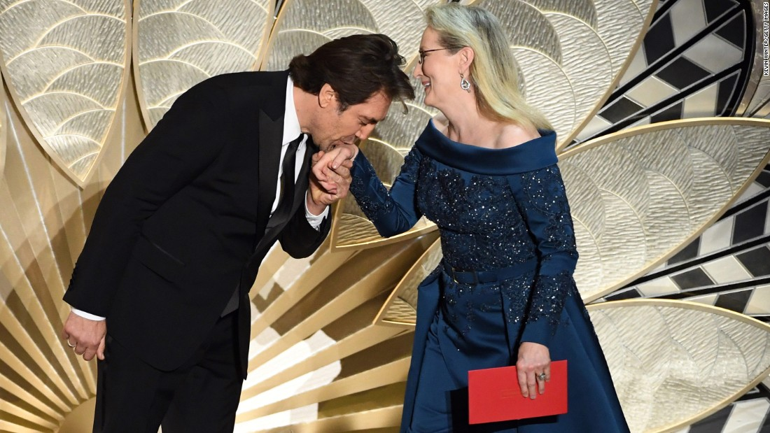 Javier Bardem kisses Meryl Streep's hand as they present an award.