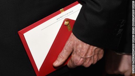 Warren Beatty holds the envelope containing the wrong award announcement for best picture.