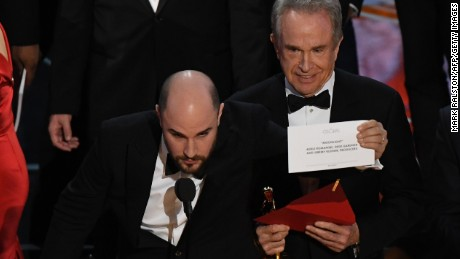 "US actor Warren Beatty (C) shows the card reading Best Film 'Moonlight"" after mistakingly reading ""La La Land"" initially at the 89th Oscars on February 26, 2017 in Hollywood, California. / AFP / Mark RALSTON        (Photo credit should read MARK RALSTON/AFP/Getty Images)"