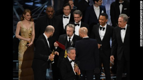 "TOPSHOT - ""La La Land"" producer Jordan Horowitz (2L) speaks to stage manager Gary Natoli (C), reading the winners card, after ""La La Land"" mistakenly won the best picture instead of ""Moonlight"" at the 89th Oscars on February 26, 2017 in Hollywood, California. / AFP / Mark RALSTON        (Photo credit should read MARK RALSTON/AFP/Getty Images)"