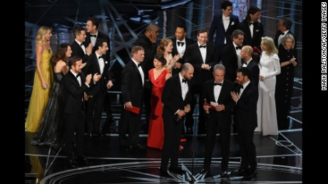 """""""La La Land"""" producer Jordan Horowitz (L) looks at the card reading Best Film 'Moonlight"""" next to US actor Warren Beatty and host Jimmy Kimmel after Beatty mistakingly read """"La La Land"""" initially at the 89th Oscars on February 26, 2017 in Hollywood, California. / AFP / Mark RALSTON  (Photo credit should read MARK RALSTON/AFP/Getty Images)"""