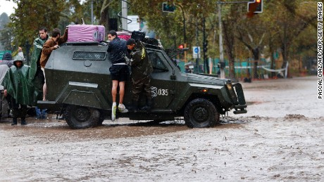 TOPSHOT - People are assisted by the police on streets flooded by the overflowing of the Mapocho river during heavy rains in Santiago on April 17, 2016. Four million people in Santiago were without tap water Sunday after unusually heavy rains pounding central Chile triggered landslides that fouled the city's water supply and forced the closure of the world's biggest copper mine, officials said. / AFP / PASCAL DIAZ        (Photo credit should read PASCAL DIAZ/AFP/Getty Images)