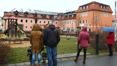 People look at the burnt-out roof truss of a former hotel that was under reconstruction to become a home for asylum seekers on February 21, 2016 in Bautzen east of Dresden, eastern Germany. According to the police, the fire broke out for still unknown reasons during the night to Sunday (February 21, 2016). Nobody was injured, as the shelter was not yet inhabited. Onlookers commented the fire with derogatory remarks on refugees. / AFP / dpa / Christian ESSLER / Germany OUT        (Photo credit should read CHRISTIAN ESSLER/AFP/Getty Images)
