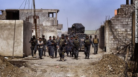 Members of the Iraqi federal police patrol the streets of Mosul as they advance on February 26, 2017 during an operation to retake the city from Islamic State (IS) group fighters. / AFP / ARIS MESSINIS        (Photo credit should read ARIS MESSINIS/AFP/Getty Images)
