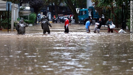 People are assisted by the police on streets flooded by the overflowing of the Mapocho river during heavy rains in Santiago on April 17, 2016. Four million people in Santiago were without tap water Sunday after unusually heavy rains pounding central Chile triggered landslides that fouled the city's water supply and forced the closure of the world's biggest copper mine, officials said. / AFP / PASCAL DIAZ        (Photo credit should read PASCAL DIAZ/AFP/Getty Images)