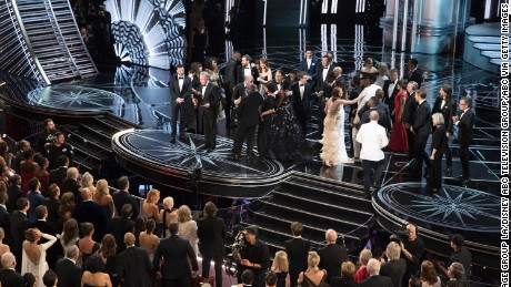 "The scene at the Oscars after ""La La Land"" was mistakenly announced as the best picture winner instead of ""Moonlight."" On stage, the casts trade places as presenter Warren Beatty explains the snafu. In the crowd, Chrissy Teigen can be seen with her hands on her head in shock."