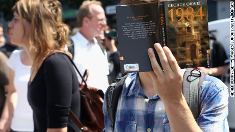 BERLIN, GERMANY - AUGUST 01:  A protester holds a German translation of George Orwell's book '1984' as he demonstrates for journalists' rights on August 1, 2015 in Berlin, Germany. After two German journalists, Andre Meister and Markus Beckedahl, reported that the German government planned to increase online surveillance, an investigation for treason, the first such case in the country against journalists in over 50 years, was brought against them and has since been suspended by the country's prosecutor-general after negative reactions from other journalists and politicians due to the implications of stifling the freedom of the press.  (Photo by Adam Berry/Getty Images)