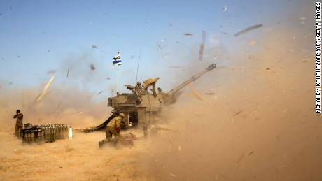 An Israeli artillery fires a 155mm shell towards targets in the Gaza Strip from their position near Israel's border with the Strip on July 12, 2014. Israel pounded Gaza for a fifth day today, vowing no let-up in its air campaign to halt rocket attacks by militants which has killed more than 120 Palestinians. AFP PHOTO /MENAHEM KAHANA        (Photo credit should read MENAHEM KAHANA/AFP/Getty Images)