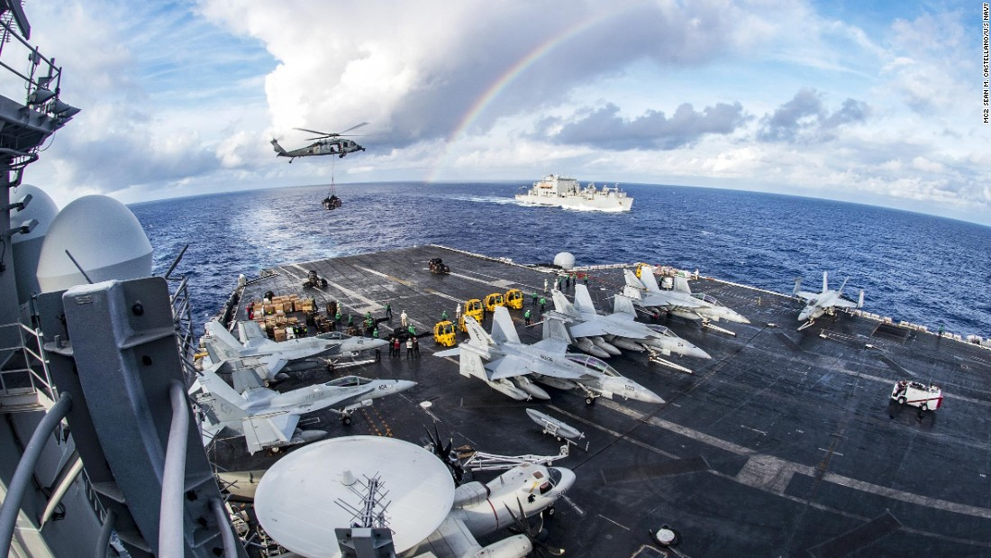 A rainbow is seen near the USS Carl Vinson, foreground, and the USNS Charles Drew during a replenishment operation in the Pacific Ocean on Friday, February 3.