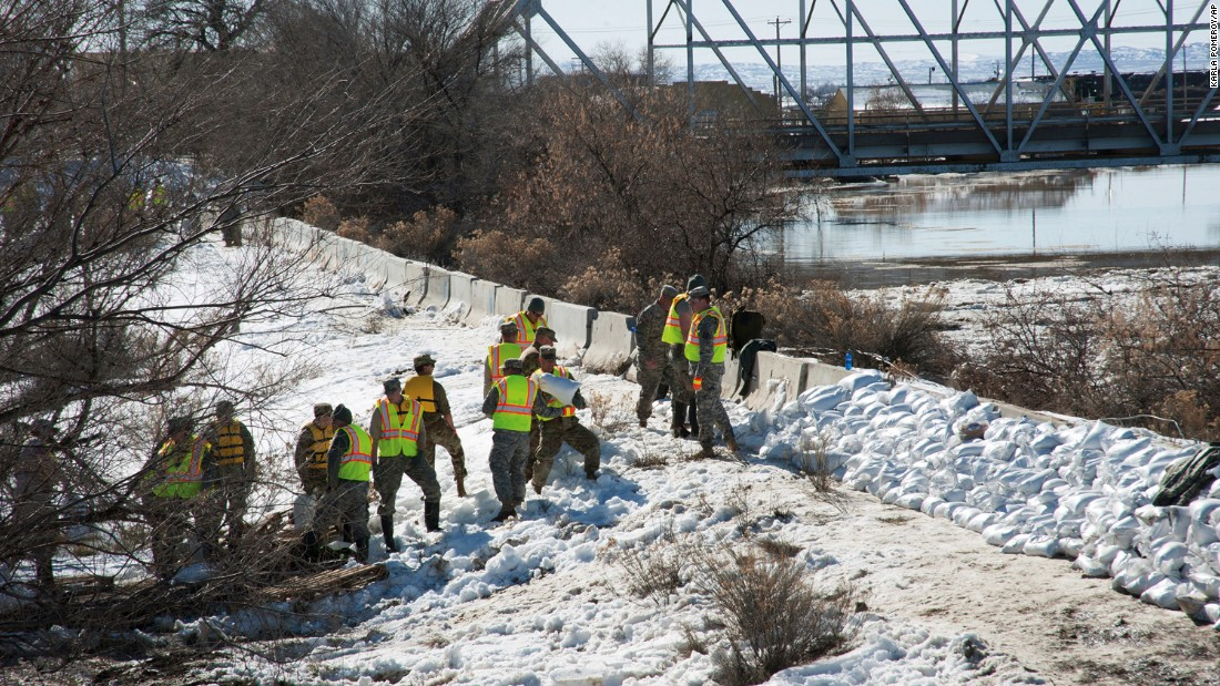 Members of the Wyoming Army National Guard help reinforce a dike along the Big Horn River in Worland, Wyoming, on Monday, February 13. Troops, firefighters and local residents stacked sandbags along the river after it jumped its banks and forced the evacuation of more than 100 homes and businesses.