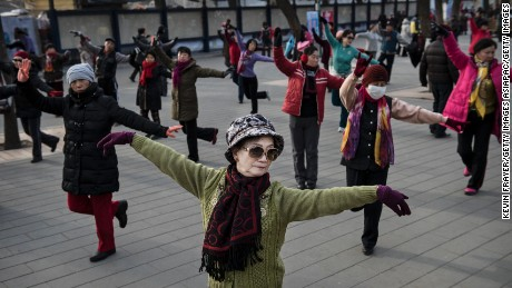 BEIJING, CHINA - DECEMBER 21: Chinese women dance as they exercise at a public park on December 21, 2014 in Beijing, China. Many Chinese, both young and old, flock to the cities parks to dance and perform martial arts for fitness. (Photo by Kevin Frayer/Getty Images)