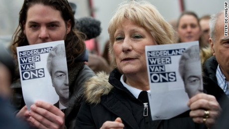 "Geert Wilders supporters hold flyers with the message ""The Netherlands ours again"" during an election campaign stop in Spijkenisse, near Rotterdam, in February."