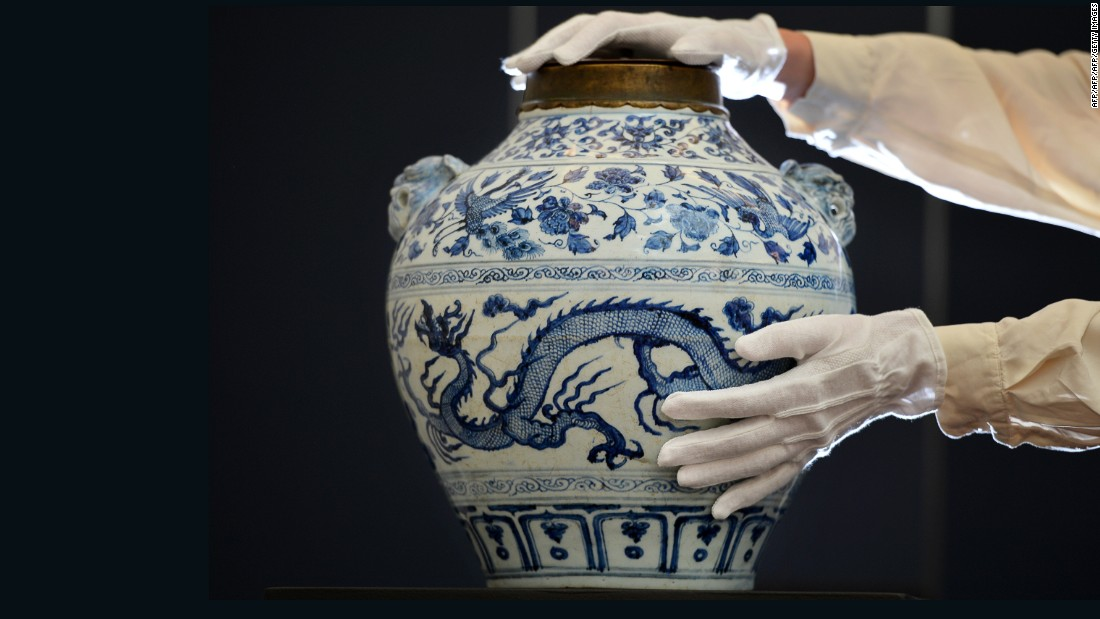 "An employee poses with a Yuan dynasty blue and white ""Dragon and Phoenix"" jar expected to realize 400,000-600,000 GBP ($637,600-$956,400USD) at auction as part of the forthcoming Sotheby's Fine Chinese Ceramics and Works of Art auction in London on November 2, 2012."