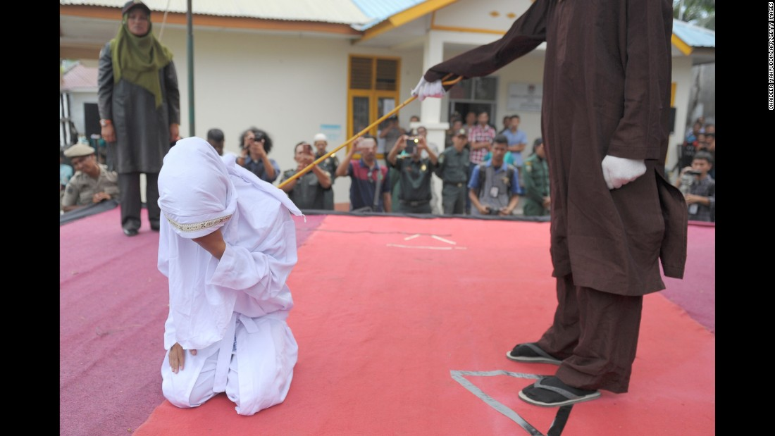 A woman is caned by a religious officer in Banda Aceh, Indonesia, on Monday, February 27. The province of Aceh is strictly Muslim and is the only province in the country implementing Sharia law. Public canings happen there regularly and often attract huge crowds. The woman here was being punished for spending time in close proximity with a man who is not her husband.
