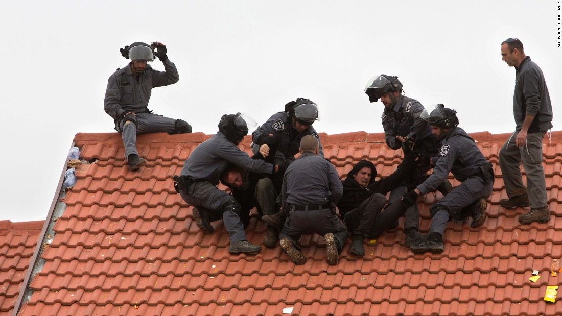 "Israeli police officers remove settlers from a rooftop in the West Bank settlement of Ofra on Wednesday, March 1. Israeli forces were demolishing nine homes in Ofra after the Supreme Court ruled they were built on private Palestinian land without a permit. Hundreds of protesters <a href=""http://www.cnn.com/2017/02/28/middleeast/ofra-protests/"" target=""_blank"">tried to resist the evacuation,</a> standing in circles and singing religious songs inside the homes."