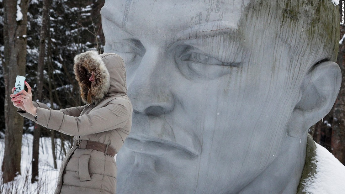 A woman takes a selfie with a statue of former Soviet leader Vladimir Lenin at a museum outside St. Petersburg, Russia, on Saturday, February 25.