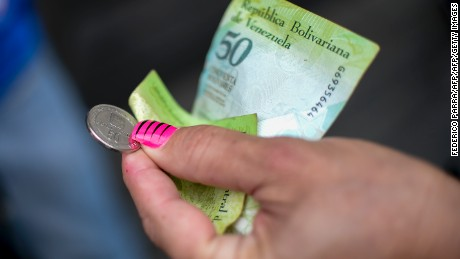 A woman pays for a coffee with a new 50-Bolivar-coin and a Bolivar-note of the same denomination in downtown Caracas on December 28, 2016.   Venezuela took delivery on December 27 of its third load of new, bigger denomination banknotes, its central bank said, but there was no sign of them in circulation yet despite official promises and mounting public anxiety. Maduro's announcement that the 100-bolivar notes would suddenly no longer be legal tender provoked long lines of people trying to change them, and looting and rioting in some areas, resulting in four deaths. / AFP / FEDERICO PARRA        (Photo credit should read FEDERICO PARRA/AFP/Getty Images)
