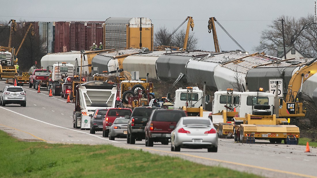 Workers look at a train that derailed in Thrall, Texas, on Monday, February 20. The rail cars were pushed over by storm winds.