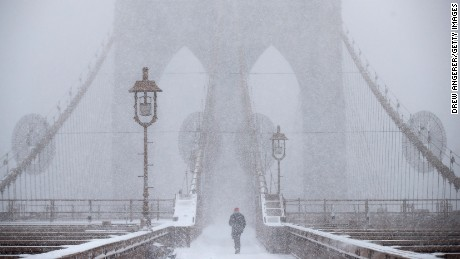 NEW YORK, NY - FEBRUARY 9: A man walks across the Brooklyn Bridge in the snow, February 9, 2017 in New York City. Following a day of 60 degree temperatures, New York City is expected to receive significant snowfall throughout the day on Thursday. (Photo by Drew Angerer/Getty Images)