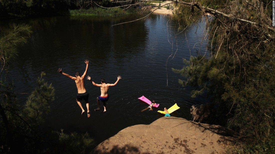 People jump into the Nepean River to cool off in Sydney on Saturday, February 11.