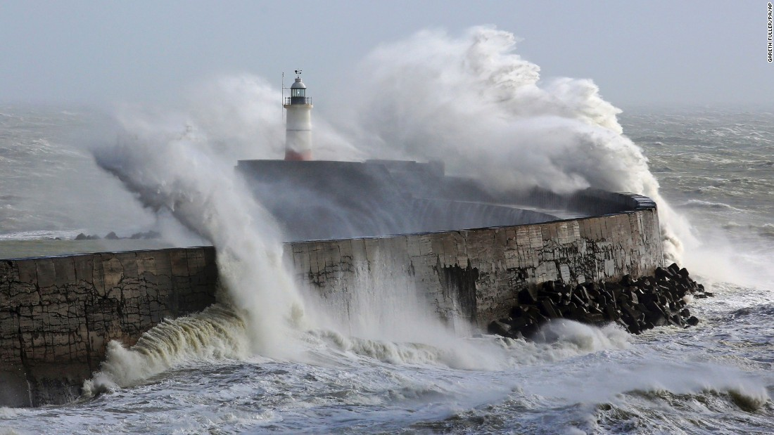 Waves crash over a lighthouse in Newhaven, England, during a storm on Thursday, February 23.