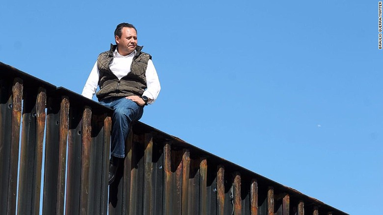 Mexican lawmaker Braulio Guerra sits atop the border fence between San Diego and Tijuana, Mexico.