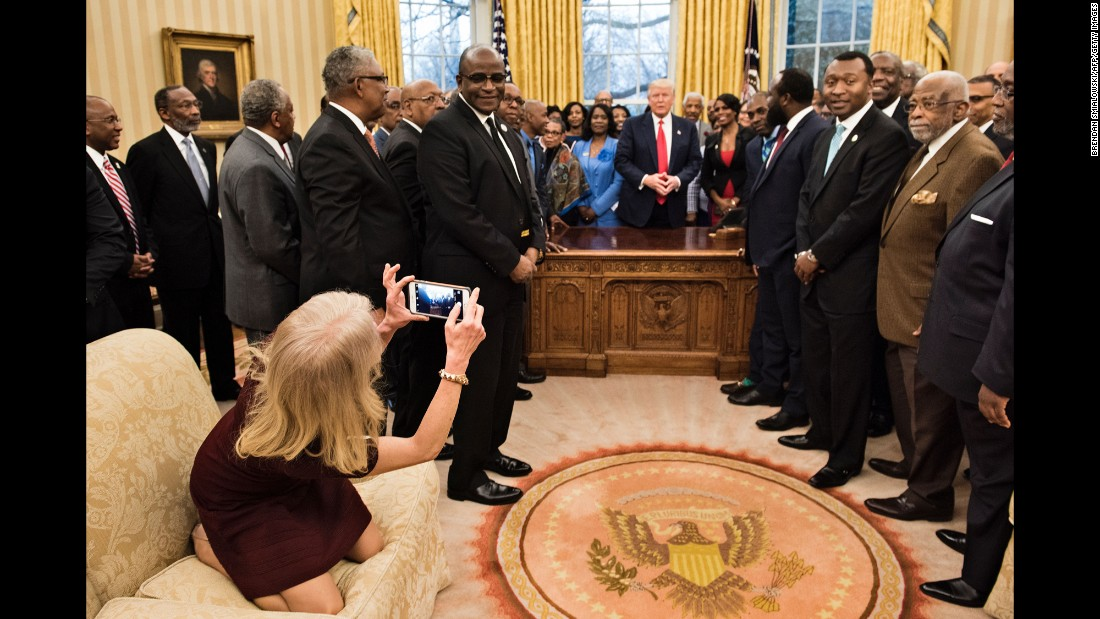 "White House Adviser Kellyanne Conway takes an Oval Office photo of President Trump and leaders of historically black colleges and universities on Monday, February 27. The image of her kneeling on the couch <a href=""http://www.cnn.com/videos/politics/2017/02/28/kellyanne-conway-oval-couch-photo-orig-vstan.cnn"" target=""_blank"">sparked memes on social media.</a>"