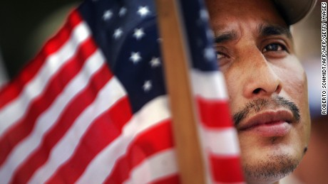 Miami, UNITED STATES: Orlando, an immigrant from Guatemala, holds a US flag as he joined hundreds of other immigrants during a rally in downtown Miami 01 May 2007. Tens of thousands of activists rallied across the United States to demand an overhaul of immigration laws and greater rights for the country's estimated 12 million illegal workers.          AFP PHOTO/Roberto SCHMIDT (Photo credit should read ROBERTO SCHMIDT/AFP/Getty Images)