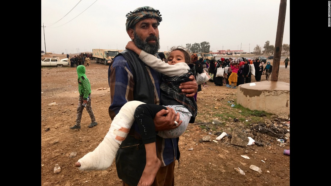 An Iraqi man carries his daughter, wounded by a mortar round that slammed into their home in the Ma'moun neighborhood of Mosul. Many of those fleeing were said to have been held as human shields by ISIS fighters while their neighborhoods became battlefields.
