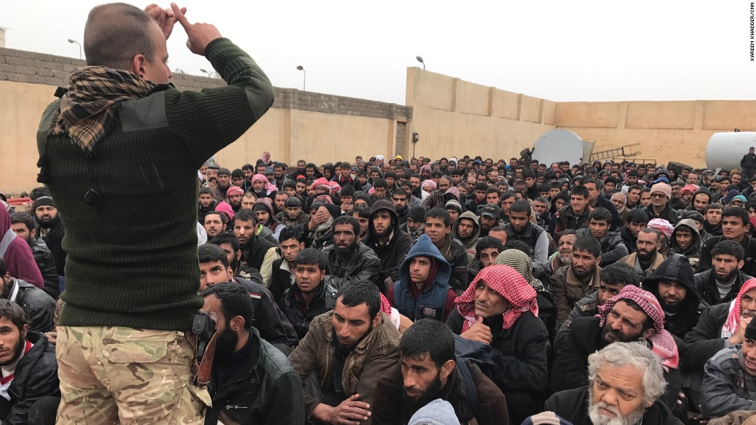 An Iraqi security officer talks to hundreds of detained men and boys who fled western Mosul. The group gathered at a processing facility south of Mosul before being transferred to nearby refugee camps.