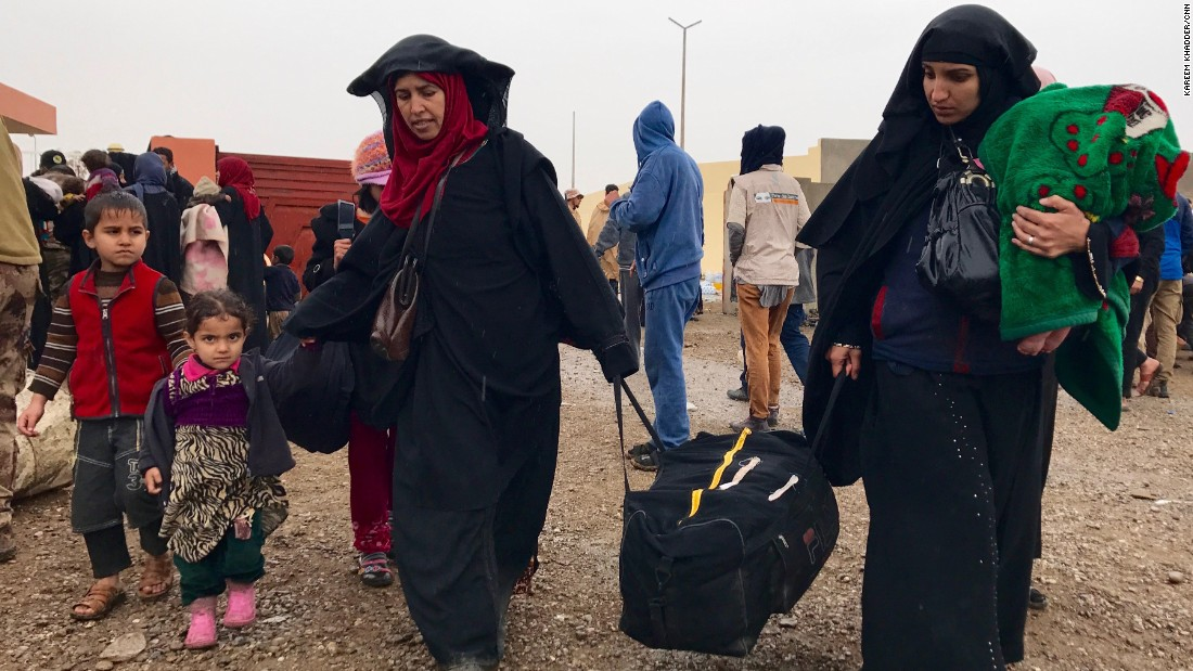 Two Iraqi women arrive with their children and a few possessions at a reception point for internally displaced people south of Mosul.