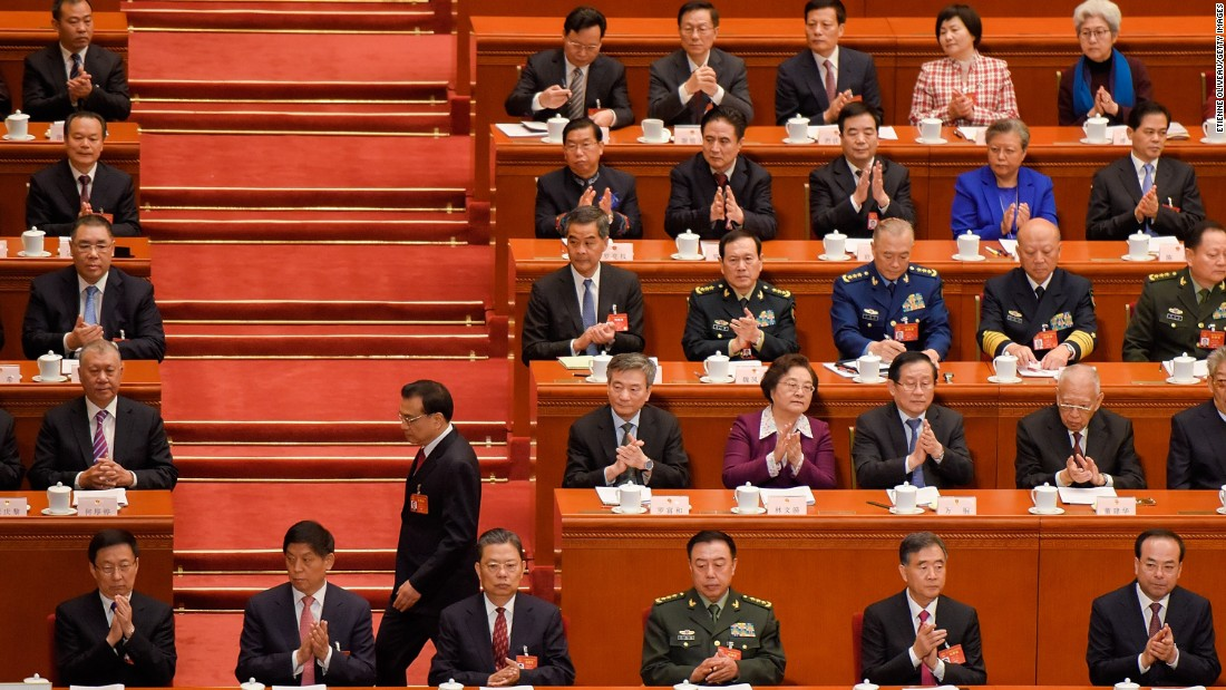 Premier Li Keqiang passes by delegates before his report during the opening session.