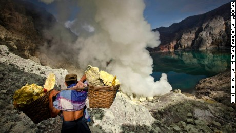 BANYUWANGI, EAST JAVA - DECEMBER 17:  A miner carries sulfur during an annual offering ceremony on the Ijen volcano on December 17, 2013 in Banyuwangi, Indonesia.  The ritual is performed by the sulfur miners of Mount Ijen who slaughter a goat and then bury the head in the crater of mount Ijenn. The sacrifice is performed to ward off potential disasters for the next year. The Ijen crater rises to 2,386m, with a depth of over 175m, making it one of the world's largest craters. Sulphur mining is a major industry in the region, made possible by an active vent at the edge of a lake, but the work is not without risks as the acidity of the water in the crater is high enough to dissolve clothing and cause breathing problems. (Photo by Ulet Ifansasti/Getty Images)