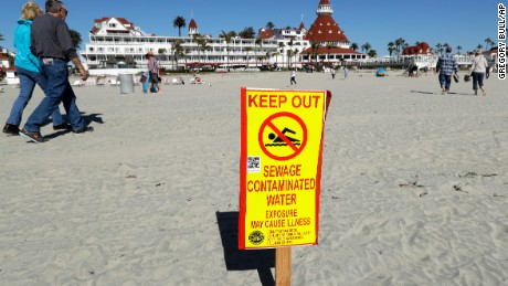A sign warns of sewage contaminated ocean waters on a beach in front of the iconic Hotel del Coronado in Coronado, California.