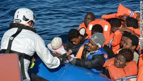 "A rescuer grabs a baby among the migrants and refugees seated on a rubber boat during a rescue operation of the Topaz Responder, a rescue ship run by Maltese NGO ""Moas"" and the Italian Red Cross, on November 4, 2016 off the Libyan coast. Around 750 migrants were rescued across the Mediterranean on November 3, 2016 by the Italian coast guard, a Frontex ship, a Save The Children vessel, German NGO Jugend Rettet's Iuventa and two boats run by the Malta-based MOAS (Migrant Offshore Aid Station). But at least 110 migrants are feared drowned after they were forced at gunpoint to set sail from Libya, while many more may have died in a separate shipwreck, survivors said. / AFP / ANDREAS SOLARO        (Photo credit should read ANDREAS SOLARO/AFP/Getty Images)"