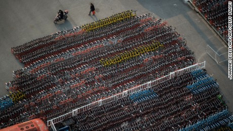A man walks past impounded bicycles from the bike-sharing schemes Mobike and Ofo in   Shanghai on March 1, 2017.