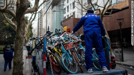This picture taken on February 20, 2017 shows an employee of a parking firm putting bicycles from the bike-sharing schemes into  a truck in Shanghai.