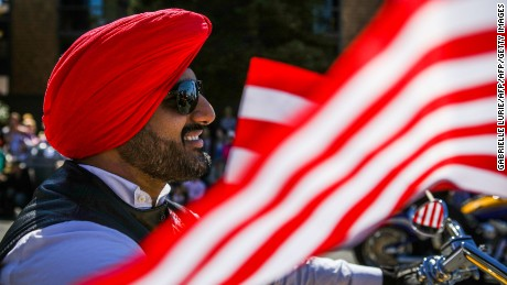 "A Sikh man rides on a motorcycle with the ""Sikh Riders of America"" group during the 4th of July Parade in Alameda, California on Monday, July 4, 2016. / AFP / GABRIELLE LURIE        (Photo credit should read GABRIELLE LURIE/AFP/Getty Images)"