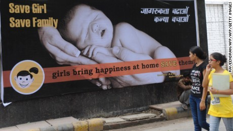 Young Indian women walk past a billboard in New Delhi on July 9, 2010, encouraging the birth of girls. Mostly as a result of sex-selective abortion, India is one of the few countries worldwide with an adverse child sex ratio in favour of boys. Under Indian law, tests to find out the gender of an unborn baby are illegal if not done for medical reasons, but the practice continues in what activists say is a flourishing multi-million-dollar business. Girls in India are often considered a liability, as parents have to put away large sums of money for dowries at the time of their marriage. AFP PHOTO/RAVEENDRAN (Photo credit should read RAVEENDRAN/AFP/Getty Images)