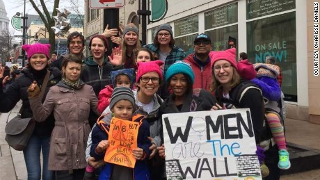 "Charisse Daniels, in the teal hat, holds a sign saying, ""Women are the wall and Trump will pay."""