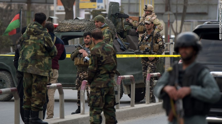Afghan security personnel gather outside the hospital.