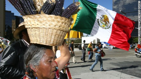 Mexico City, MEXICO: A peasant woman who carries a basket full of cobs on her head, leads 31 January, 2007 in Mexico City a demonstration against the price rise of corn, basic food of the low income people in Mexico. The government has topped the corn tortilla at 8.50 Mexican pesos (USD 0.80). AFP PHOTO/Omar TORRES (Photo credit should read OMAR TORRES/AFP/Getty Images)