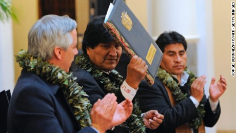Bolivian President Evo Morales (C), accompanied by Vice-President Alvaro Garcia Linera (L) and Rural Development and Lands Minister Cesar Cocarico, promulgates a government bill increasing the legal areas of cultivation of coca, at the Quemado presidential palace in La Paz, on March 8, 2017. Under the new law, the legal cultivation area for the country's two main coca-growing regions would be extended from 12,000 hectares to 22,000 -- capped at 14,300 hectares for the Los Yungas region and 7,700 hectares in the Chapare region, where Morales used to grow coca. / AFP PHOTO / JORGE BERNAL        (Photo credit should read JORGE BERNAL/AFP/Getty Images)