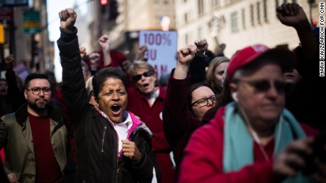 "Gloria Brown, 55, cheers during a rally in New York. She said she missed a little bit of work to join the protests. ""I'm here because I'm a woman, but I'm also here because of the lack of equality that women face,"" she said. ""I want to show that we do have power by supporting each other. We have to keep fighting for our rights."""