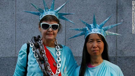 """Barbara Skinner, 56, and Vi Huynh, 55, protest outside the U.S. Immigration and Customs Enforcement office in San Francisco. """"I feel strongly that our liberties are at risk especially with this administration,"""" Skinner said.  Huynh said she came out """"because today is International Women's Day and I wanted to march and rally with my sisters and allies."""""""