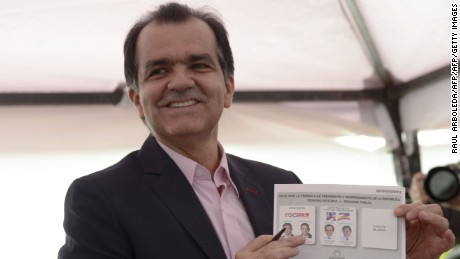 Colombian presidential candidate for the Democratic Center party, Oscar Ivan Zuluaga, casts his vote during the presidential runoff election, in Bogota, on June 15, 2014. Colombians went to the polls Sunday in a cliffhanger presidential election that has become a referendum on peace talks with leftist guerrillas. Voters will choose between President Juan Manuel Santos, who is seeking a second term, and Oscar Ivan Zuluaga, a vehement critic of the president's peace talks with the Revolutionary Armed Forces of Colombia (FARC).   AFP PHOTO/Raul ARBOLEDA        (Photo credit should read RAUL ARBOLEDA/AFP/Getty Images)