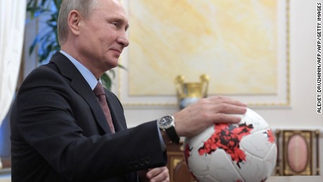 "Russian President Vladimir Putin places his hand on an official match ball for the 2017 FIFA Confederations Cup, named ""Krasava"""