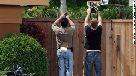"Paparazzi look over the fence outside the home of Mildred Patricia Baena, the former maid who mothered a child by actor and former Californian Governor Arnold Schwarzenegger, in Bakersfield, California on May 18, 2011.  Film star turned politician Arnold Schwarzenegger admitted Tuesday to fathering a lovechild with a staff member which he kept secret for a decade, until its disclosure torpedoed his marriage. The former bodybuilder's estranged wife Maria Shriver, a daughter of the Kennedy political dynasty, reacted by asking for privacy during a ""painful and heartbreaking time,"" while their children rallied round the family. A power couple married for 25 years, Schwarzenegger and Shriver announced their separation last week, four months after the former ""Terminator"" star left office as California governor in January.          AFP PHOTO/Mark RALSTON (Photo credit should read MARK RALSTON/AFP/Getty Images)"