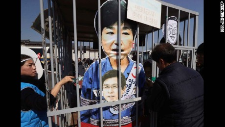 Protesters in Seoul, South Korea, look at cut-outs of impeached President Park Geun-hye, top, and acting leader and Prime Minister Hwang Kyo-ahn, bottom, in a mock jail as they march Friday toward the presidential house after the Constitutional Court voted to oust Park.