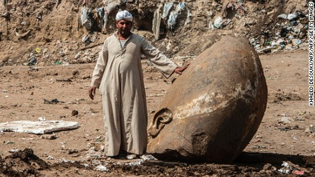 An Egyptian worker stands next to the head of statue at the site of a new discovery by a team of German-Egyptian archeologists in Cairo's Mattarya district on March 9, 2017. Statues of the kings and queens of the nineteenth dynasty (1295 - 1185 BC) were unearthed in the vicinity of the Temple of Ramses II in what was the old Pharonic city.  / AFP PHOTO / KHALED DESOUKI        (Photo credit should read KHALED DESOUKI/AFP/Getty Images)